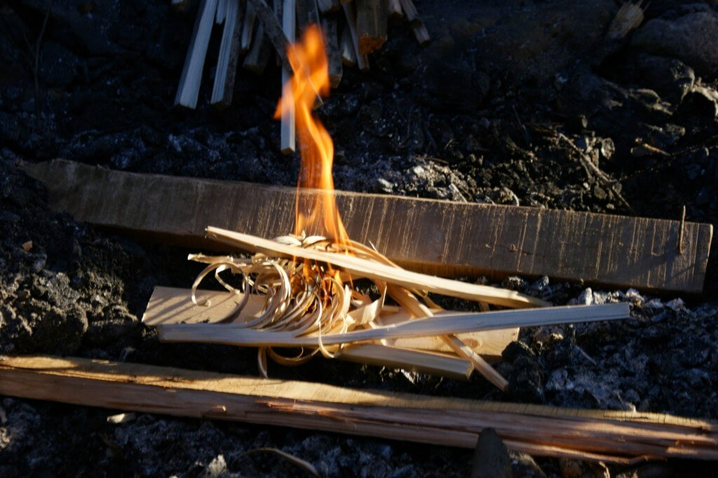 Lighting a fire with feather sticks and using some of the wood to reflect heat back into the fire