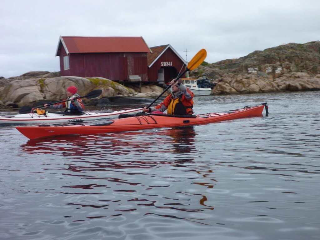 A sea kayaker with pink granite island in the background off western sweden