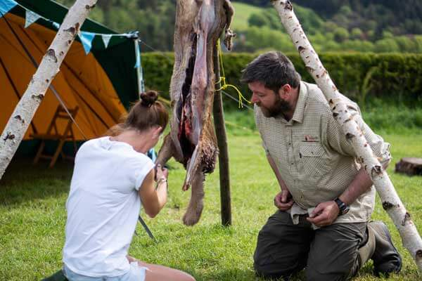 Jamie from the Wild Bushcraft Company showing how to butcher a deer at the Carrog Tentipi Camp