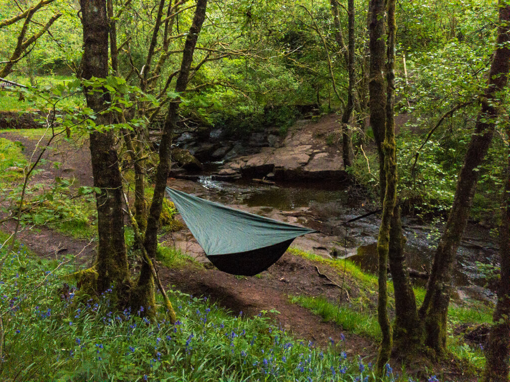 A Hennessy Hammock between two trees, in woodland by a stream