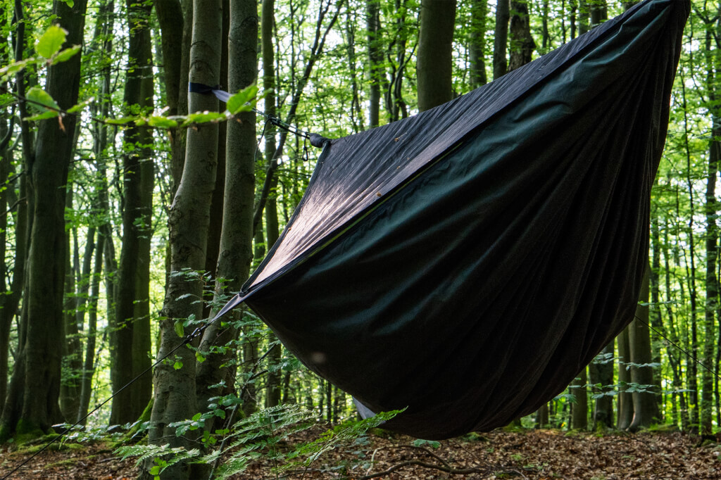 A hennessy hammock pitched in green woodland