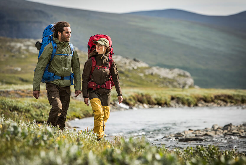 Trekking by a river in Fjallraven clothing